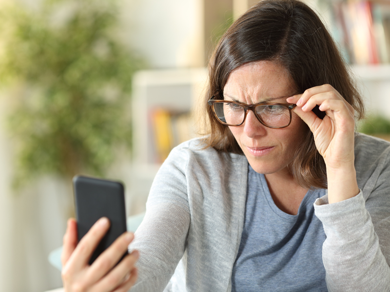middle-aged woman wearing glasses and straining to see her phone